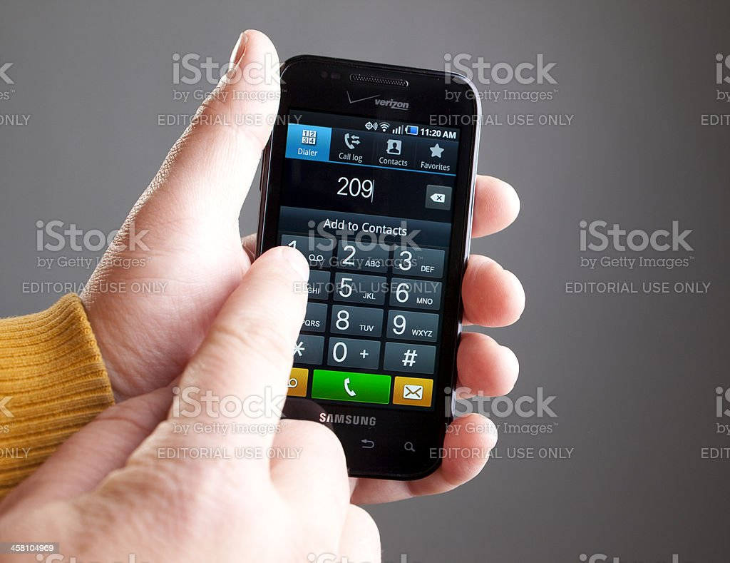 Man's hands using an Android smartphone dial pad royalty-free stock photo