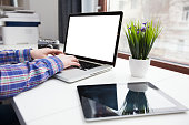 Man's hands using laptop with blank screen