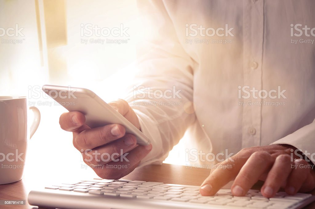 Man's hands using smart phone and computer at office desk stock photo