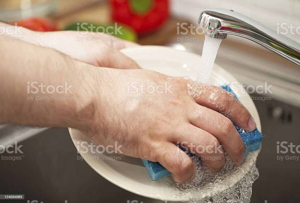 man's hands washing dishes stock photo