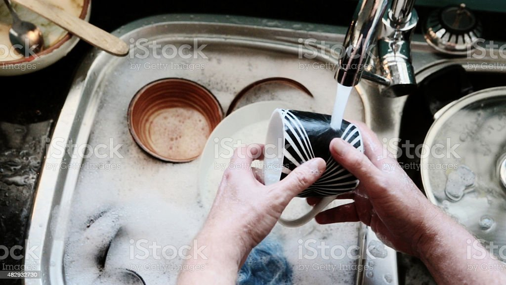 Man's hands washing dishes, seen from overhead. stock photo