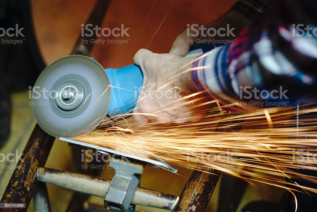 Man's Hands with an Angle Grinder stock photo