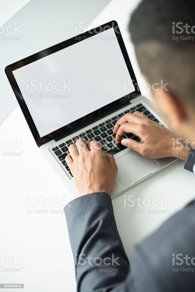 Man's hands working on a laptop keyboard stock photo