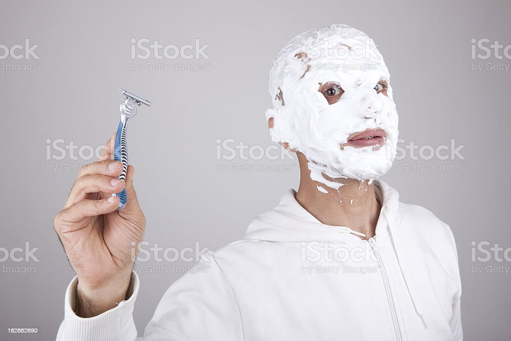Man's head completely covered in shaving cream holding razor royalty-free stock photo