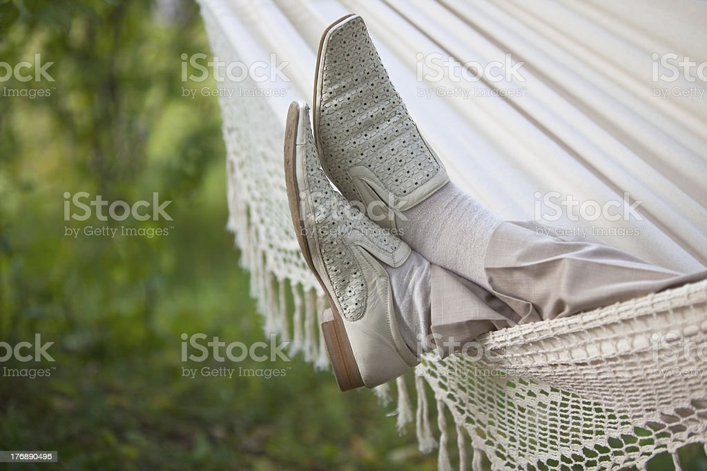 man's legs in hammock stock photo