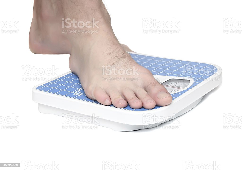 Man's legs ,which weighed on floor scale. Isolated royalty-free stock photo