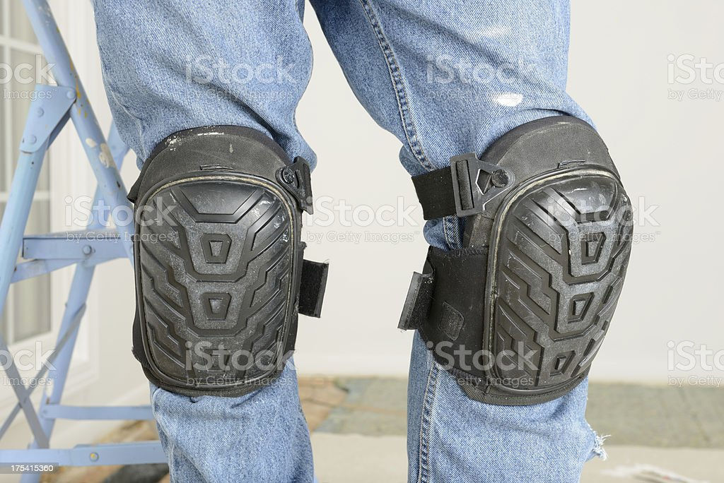 Man's Legs With Kneepads In Room Under Renovation stock photo