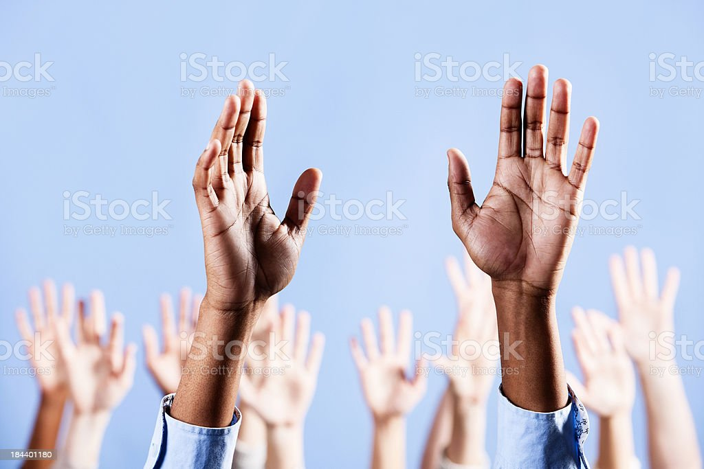 Man's raised hands with many more in background royalty-free stock photo