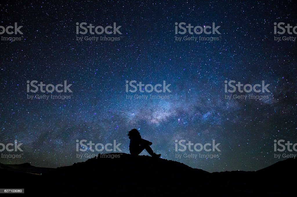 Man's silhouette sitted, staring at the milky way stock photo
