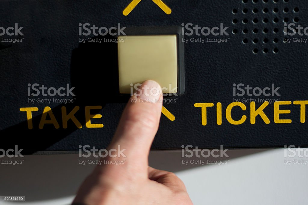 Man's Thumb Pressing 'TAKE TICKET' Button at Parking Garage (Close-Up) stock photo