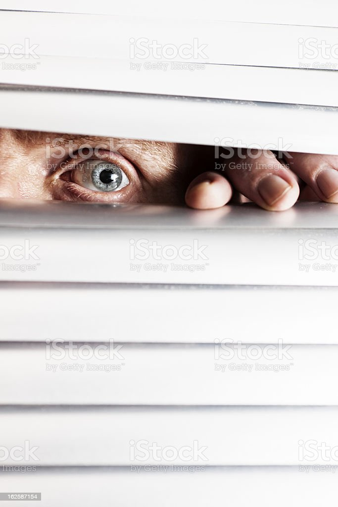 Man's worried-looking eye peeps out through closed venetian blinds stock photo