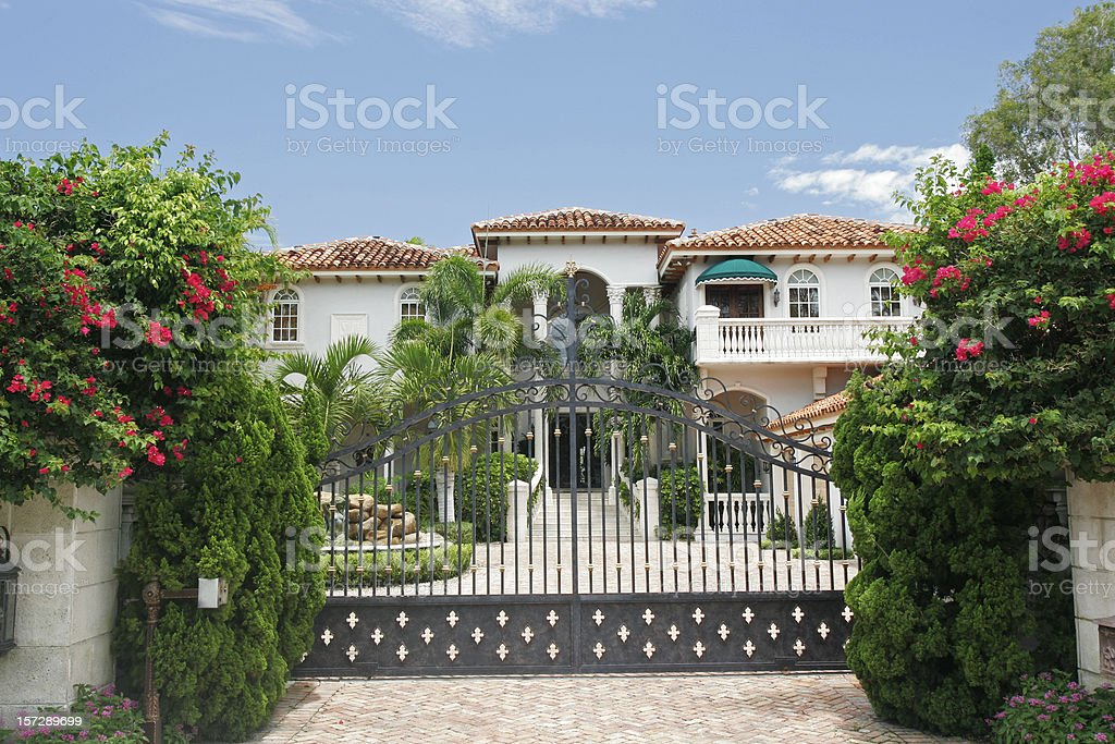 Mansion behind a gate surrounded by tropical greenery stock photo