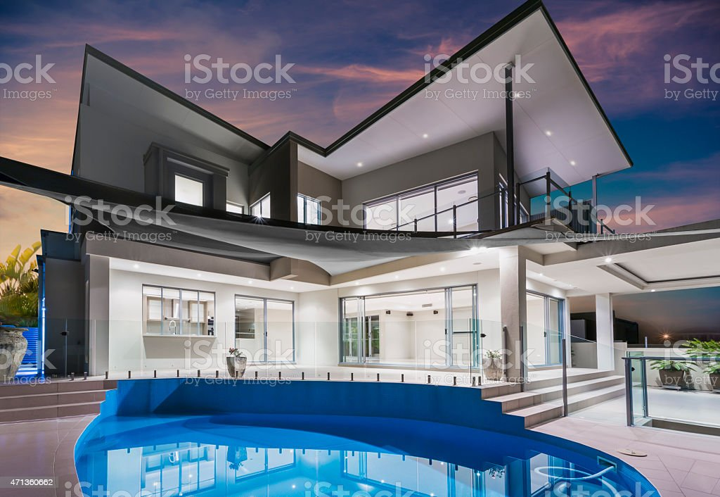 Mansion with pool and beautiful sky at dusk stock photo
