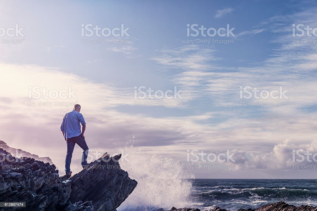 Manstanding on a rock overlooking the sea. stock photo