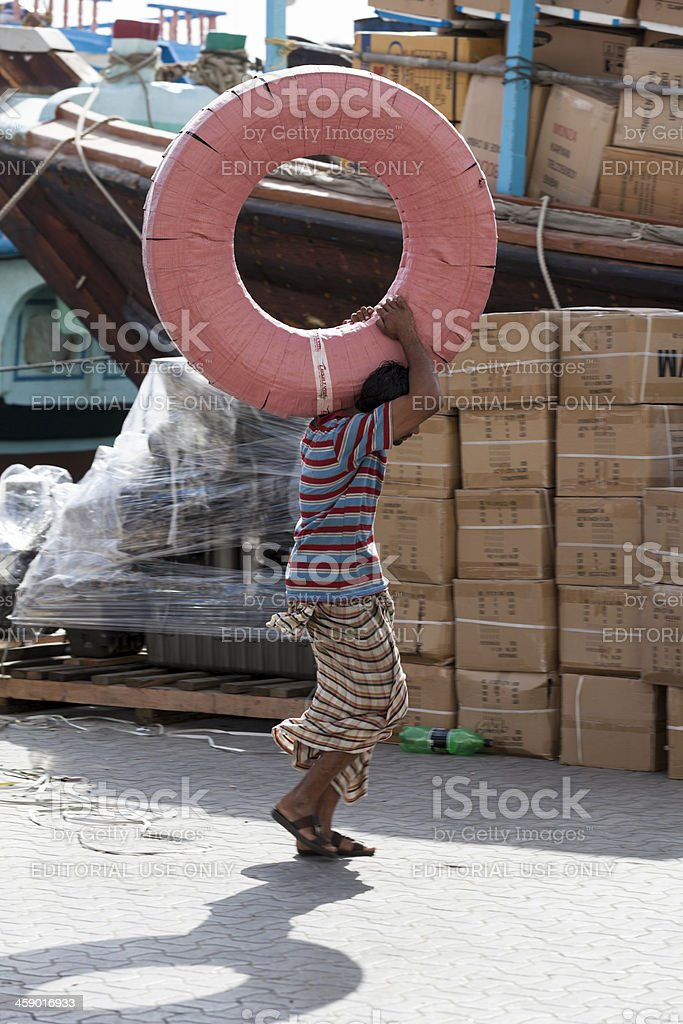 Manual worker at the Dubai Creek carying a big package royalty-free stock photo
