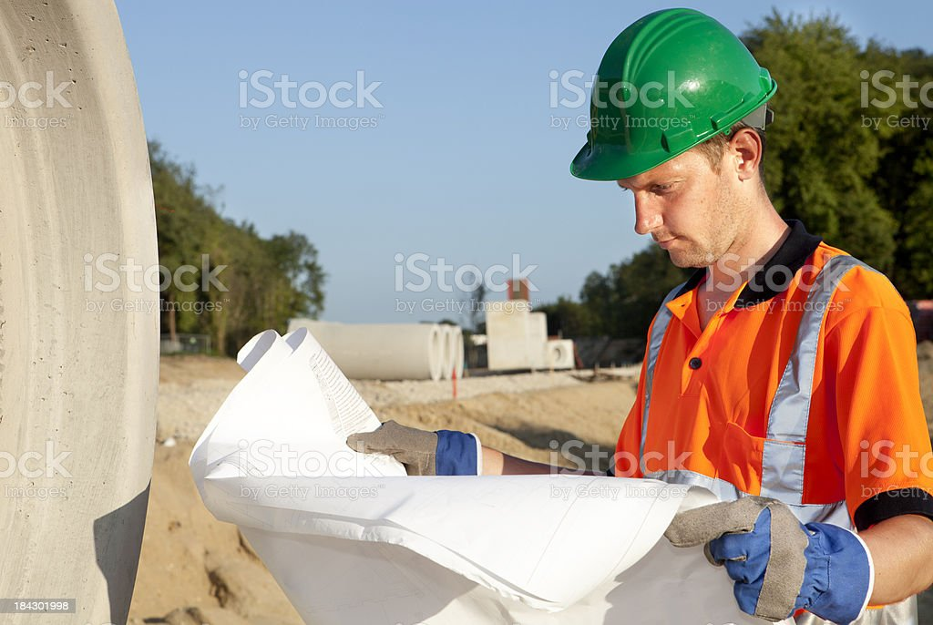 Manual worker busy with road construction. Sewer on background. royalty-free stock photo