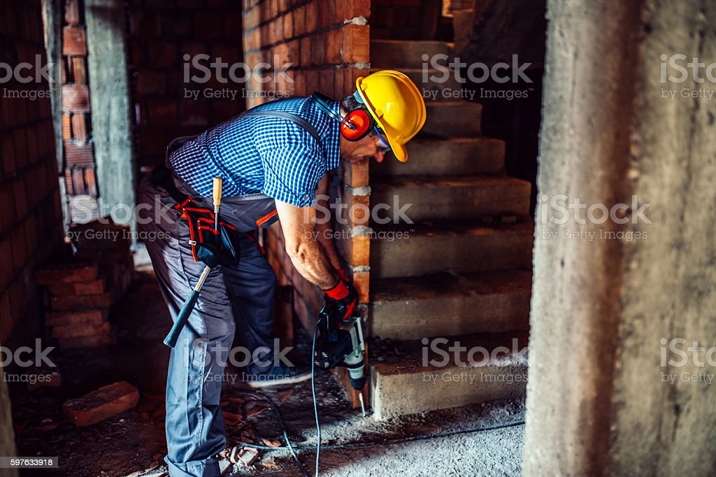 Manual worker drilling stock photo