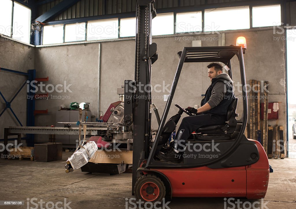 Manual worker driving a forklift in a distribution warehouse. stock photo