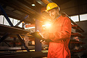 Manual worker going through paperwork in aluminum mill.