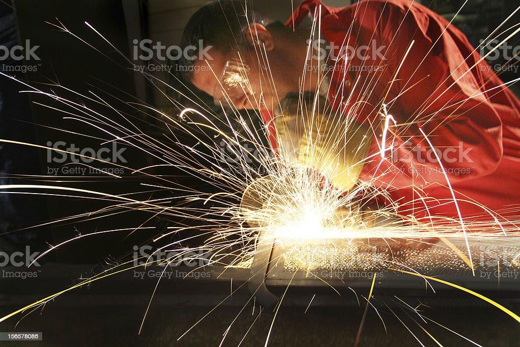 Manual worker grinding metal in an industrial workshop royalty-free stock photo