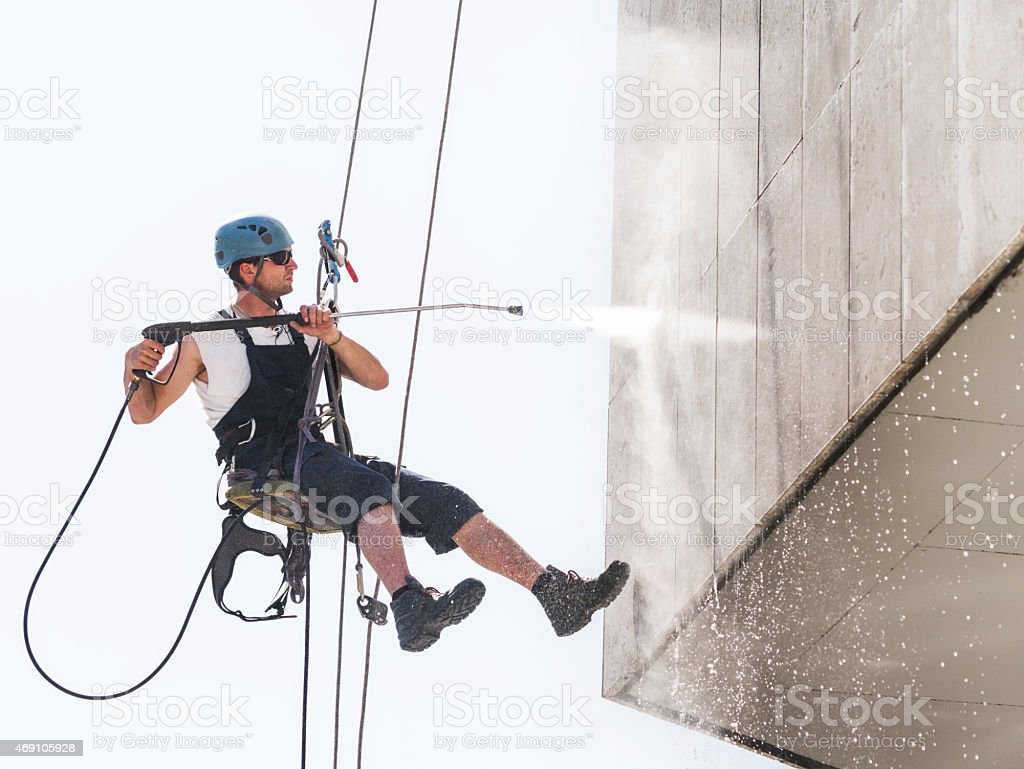 Manual worker hanging high up and washing a building. stock photo