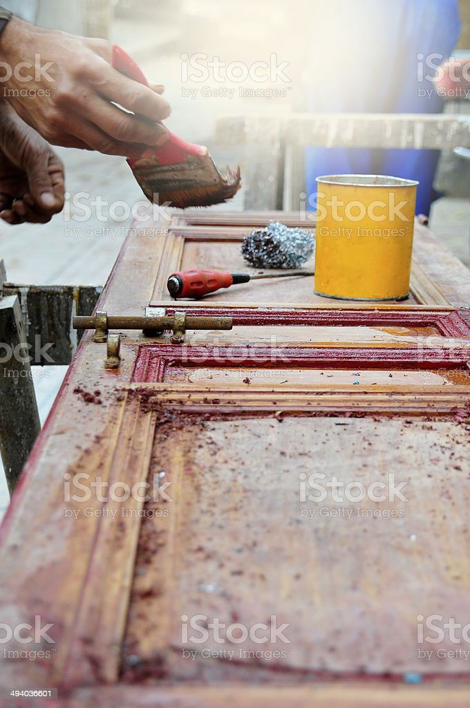 Manual worker is painting and refurbishing the wooden door royalty-free stock photo