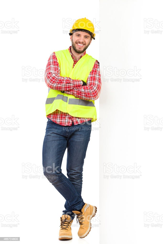 Manual worker leaning on a big white placard stock photo
