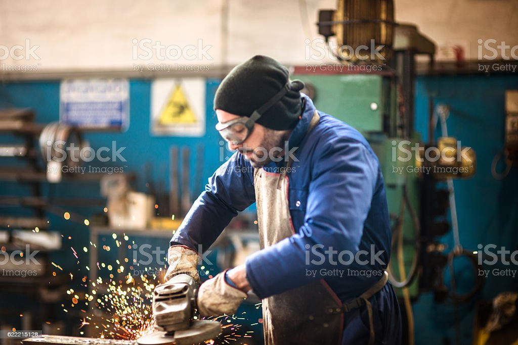 manual worker on a workshop with the grinder stock photo