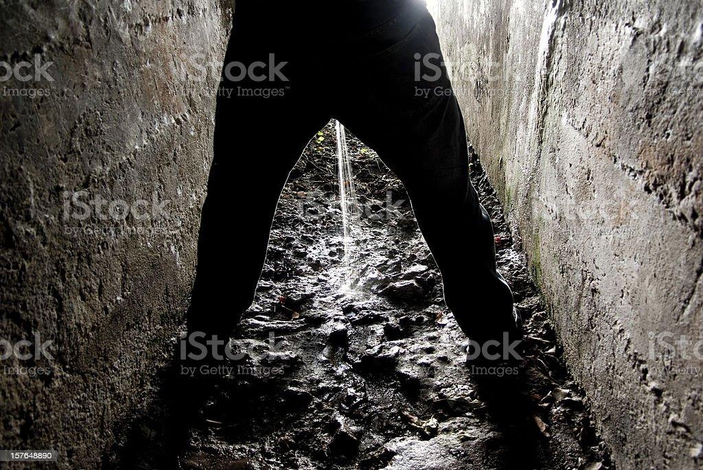 manual worker peeing - dark gloomy dungeon of despair stock photo