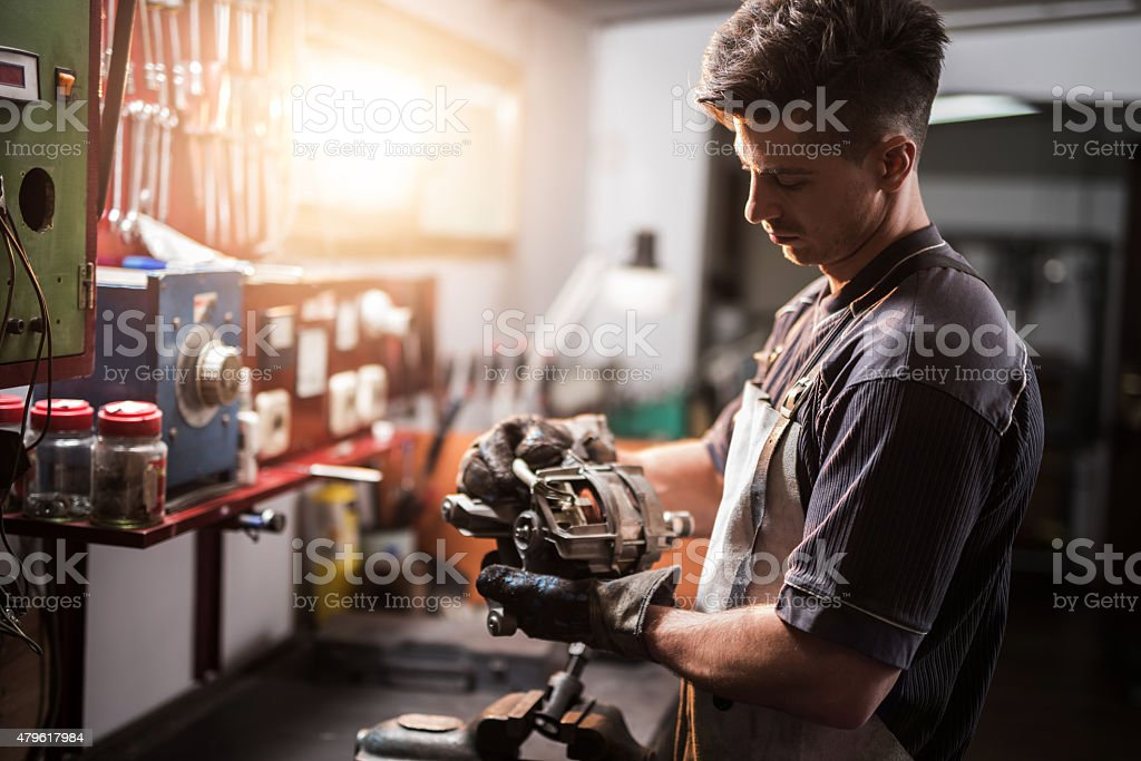 Manual worker repairing electric motor in a workshop. stock photo