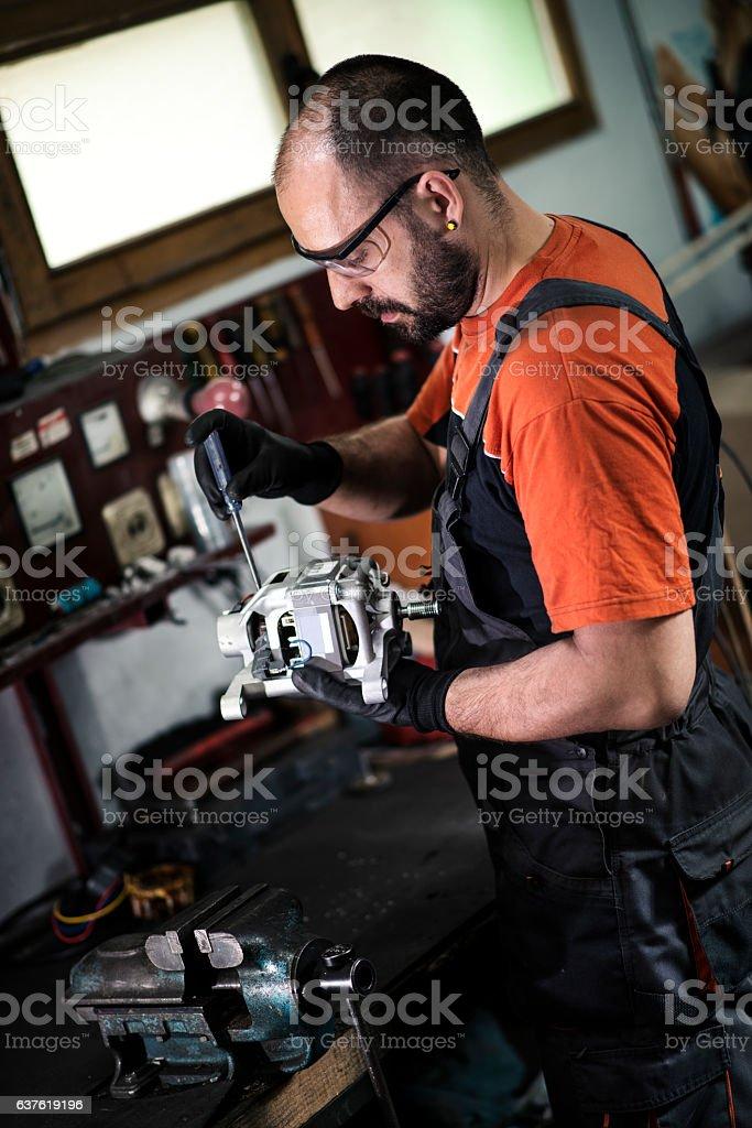 Manual worker repairing electric motor in a workshop. stock photo