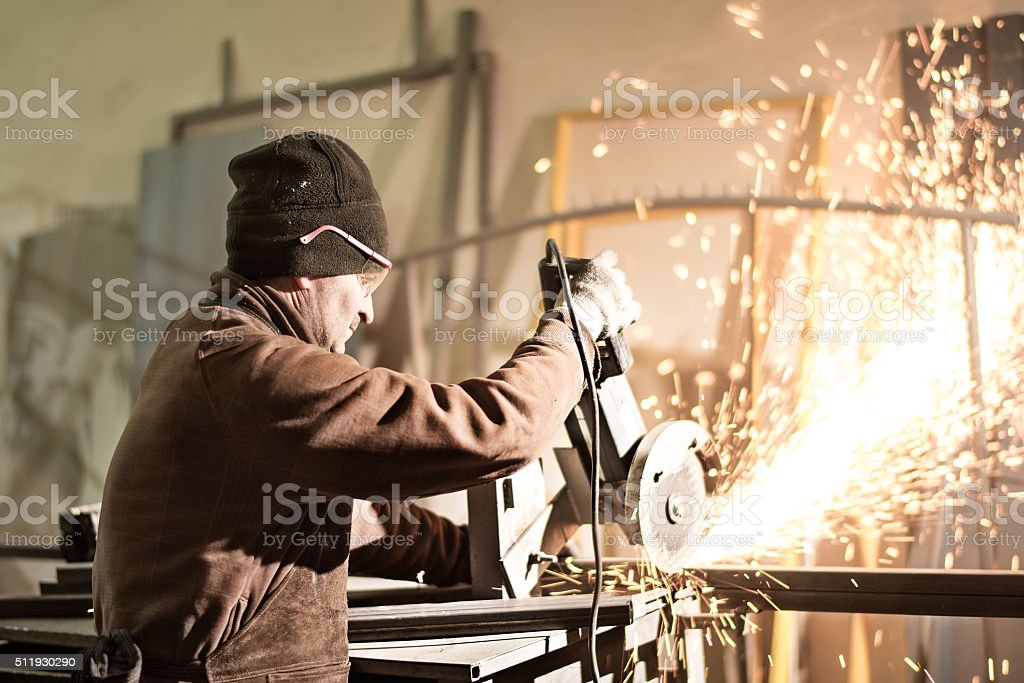 Manual worker using grinder in workshop stock photo