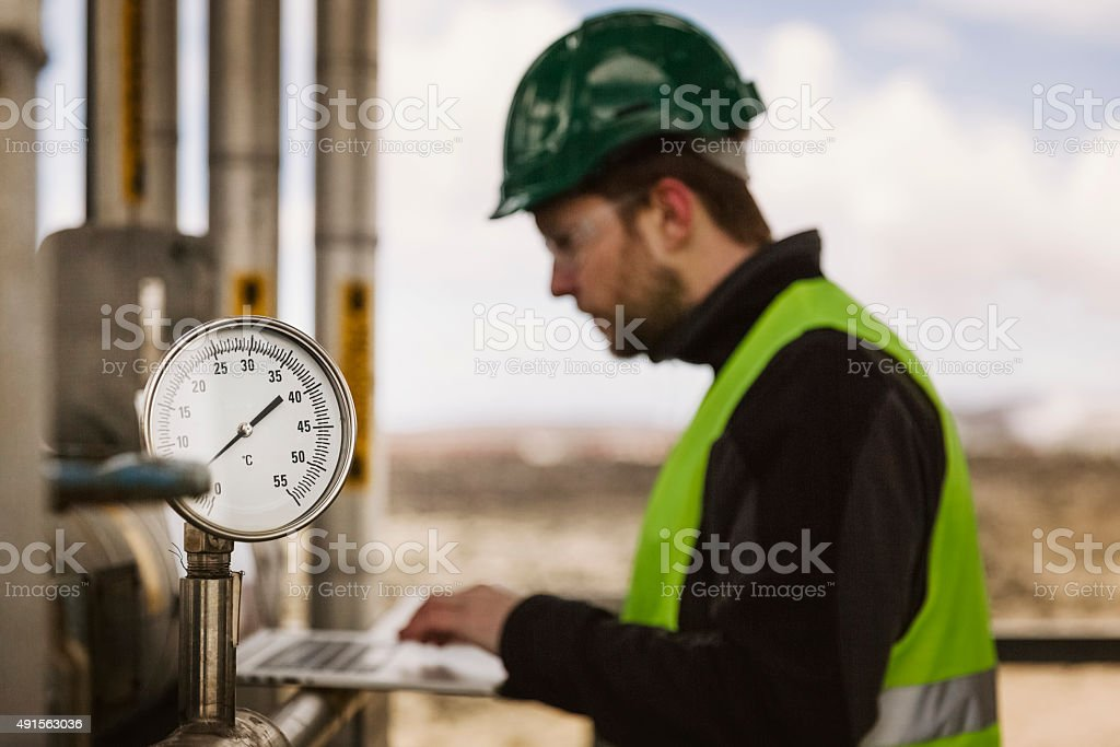 Manual worker using laptop by industrial gauge stock photo