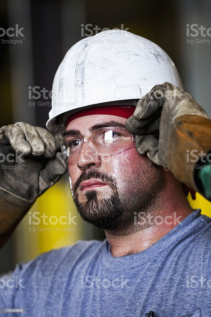 Manual worker wearing hardhat and safety glasses royalty-free stock photo