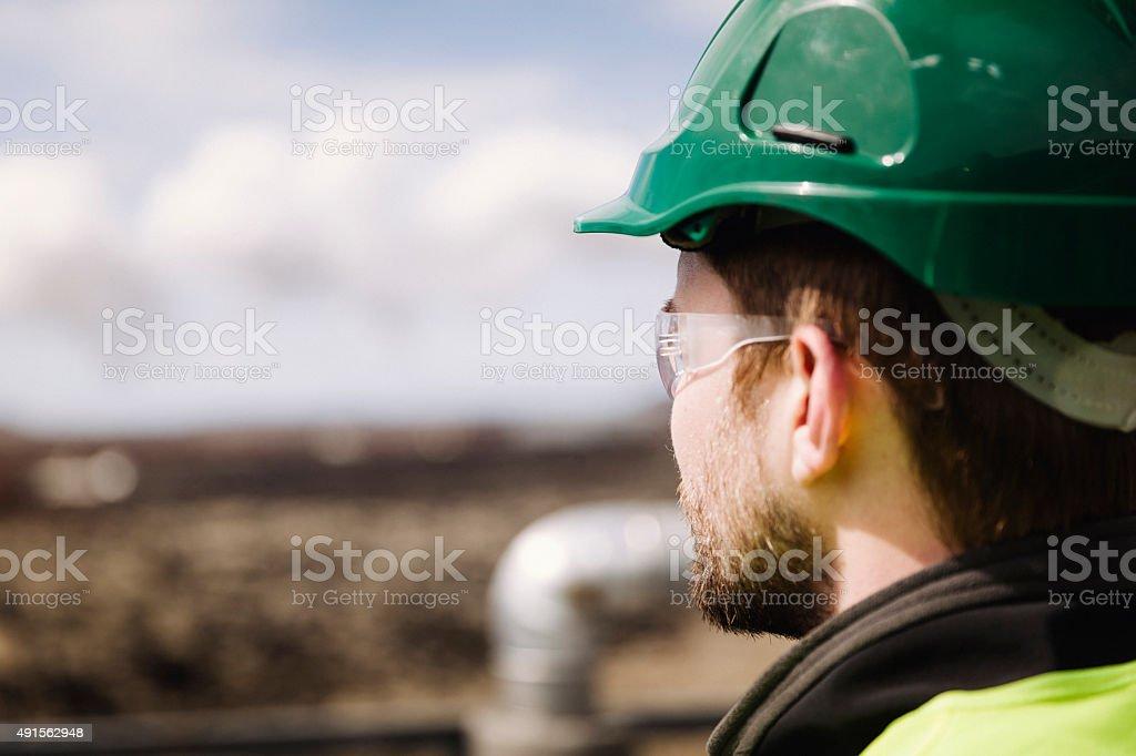 Manual worker wearing hardhat looking away stock photo
