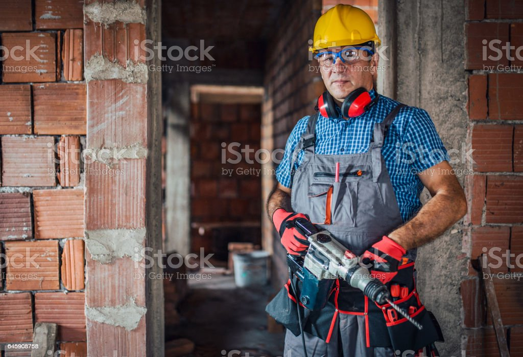 Manual worker with a drill stock photo
