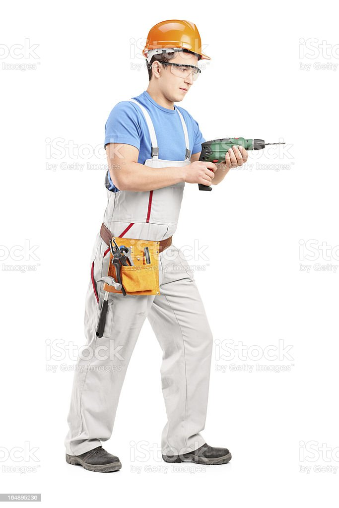 Manual worker with helmet using a drill tool royalty-free stock photo