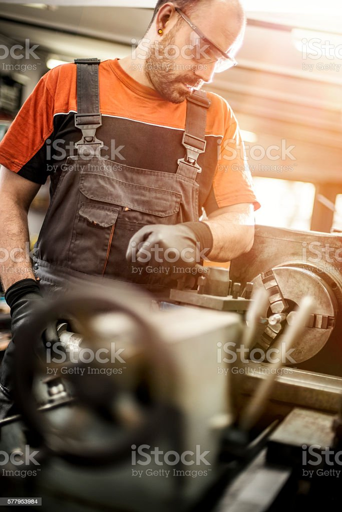 Manual worker working on a machine in a workshop stock photo