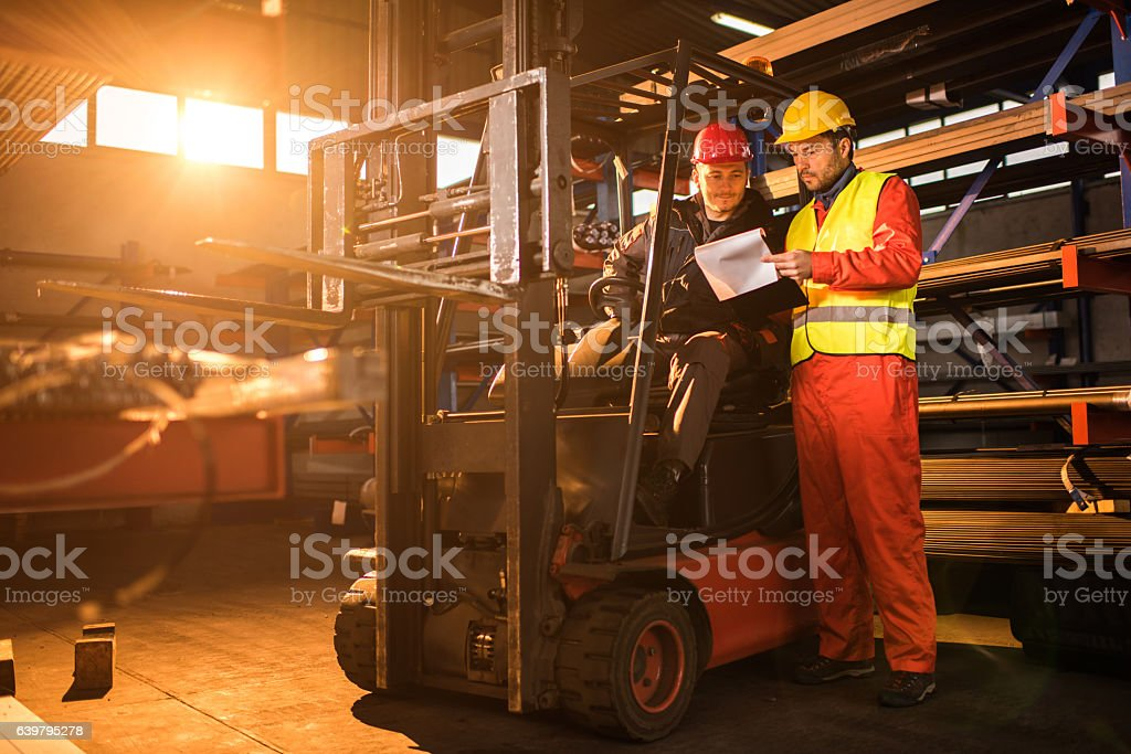 Manual workers going through paperwork in aluminum mill. stock photo