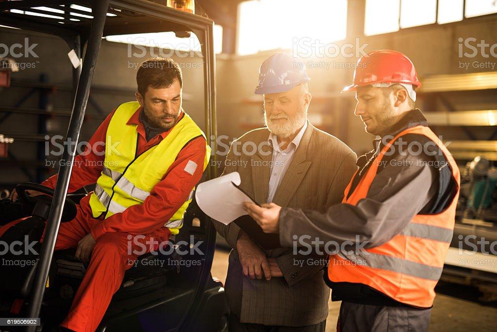 Manual workers going through paperwork with their manager in factory. stock photo