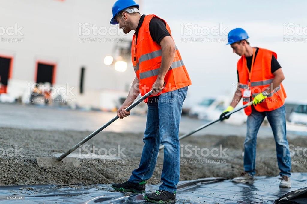 Manual workers leveling concrete stock photo