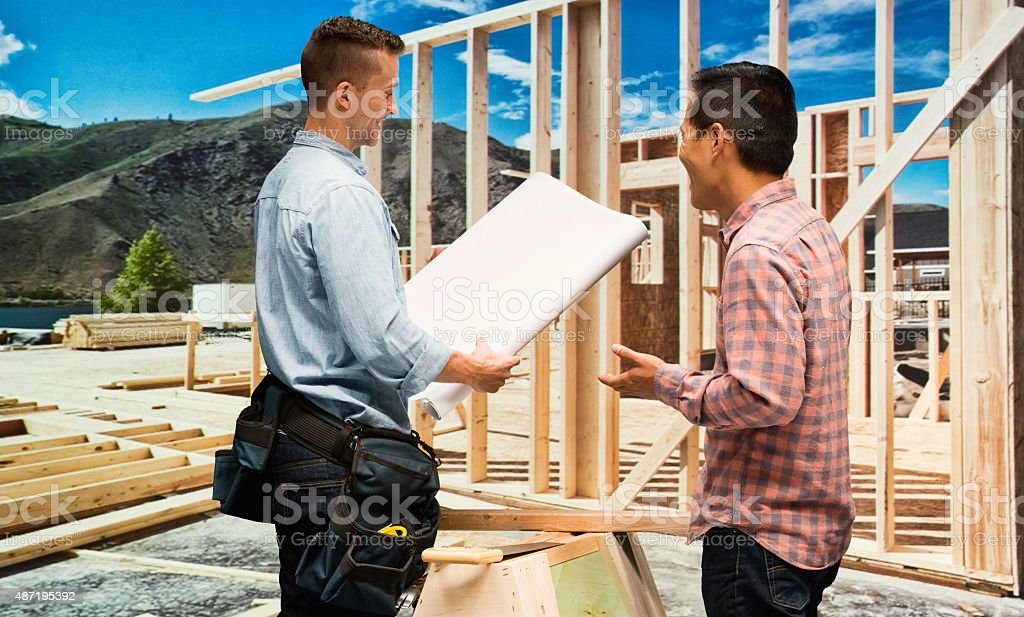 Manual workers looking at blueprints stock photo