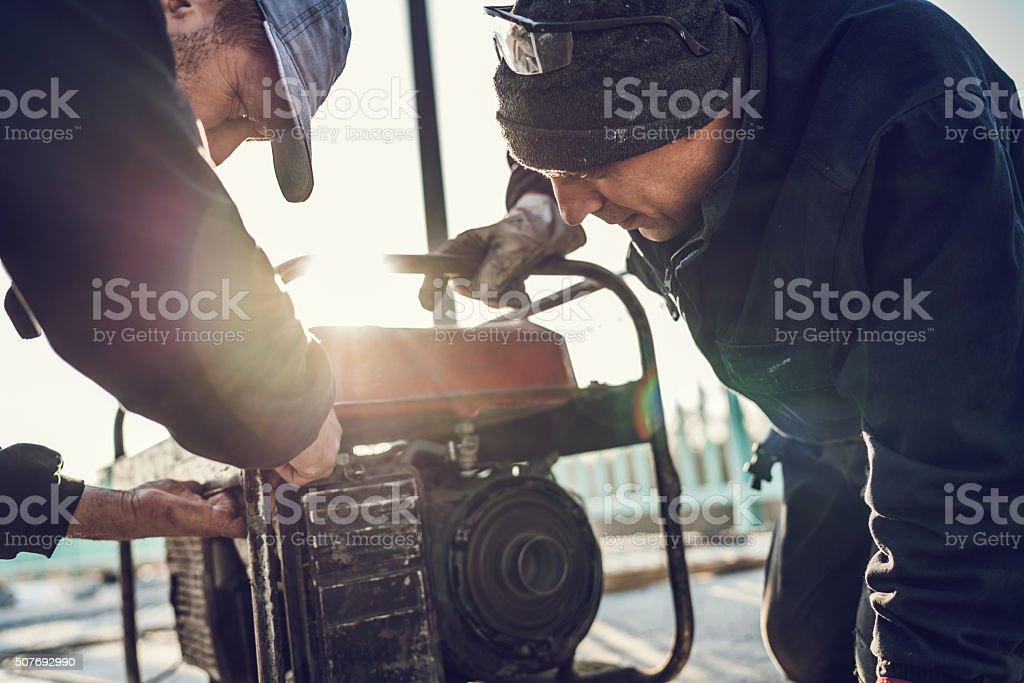 Manual workers repairing power generator. stock photo