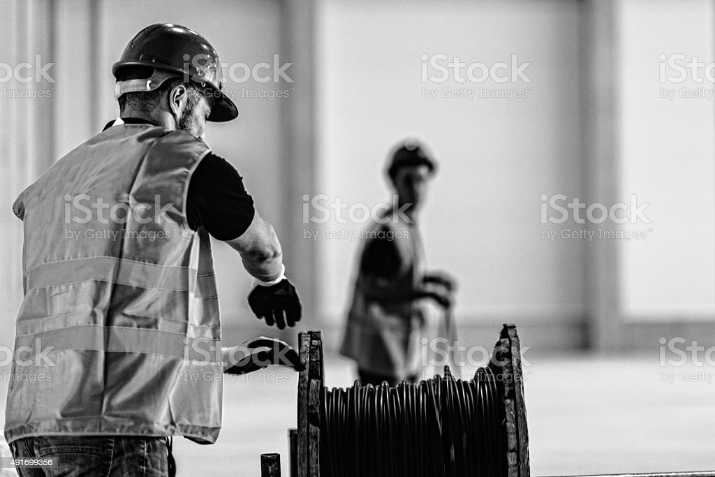 Manual workers spining out cable stock photo