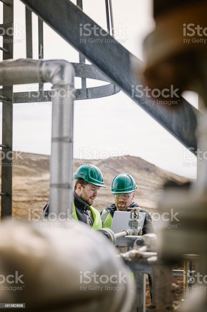 Manual workers using laptop in factory stock photo