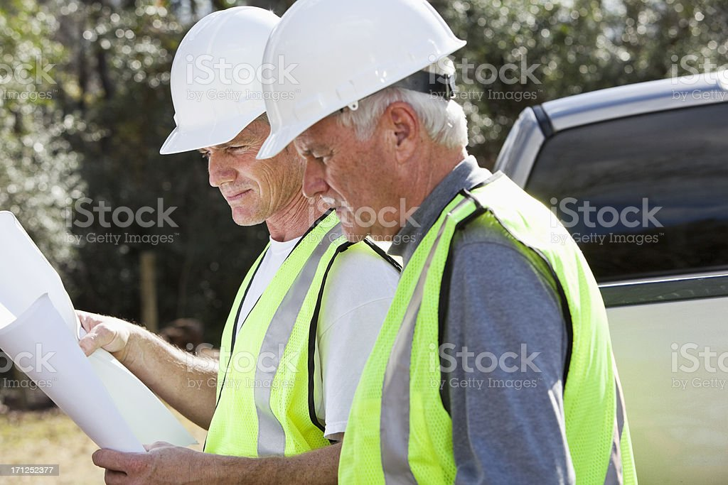 Manual workers wearing hardhat and safety vest royalty-free stock photo