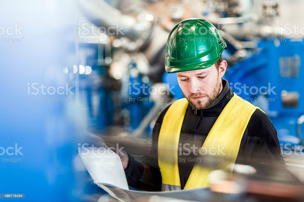 Manual working reading document in factory stock photo