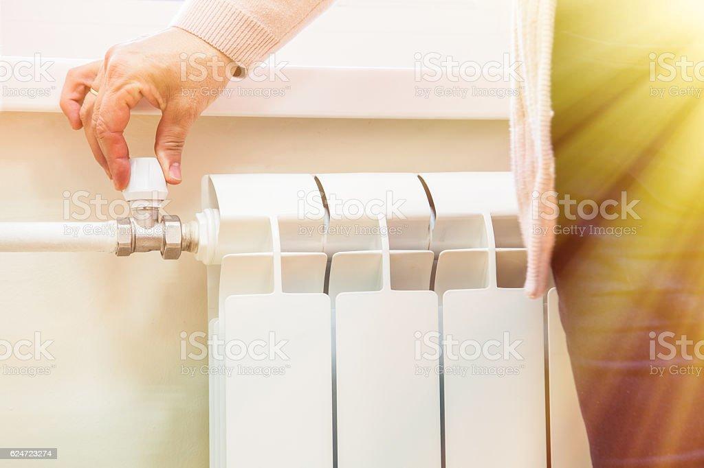 manually adjust the volume of heating valve on the radiator stock photo