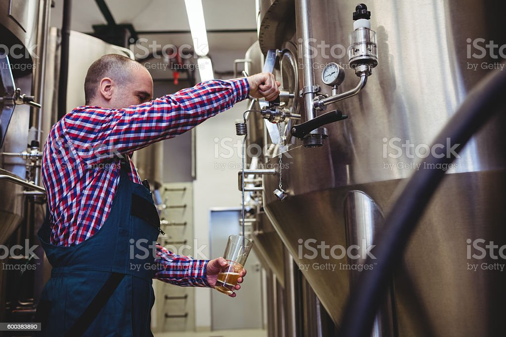 Manufacturer filling beer from storage tank at brewery stock photo