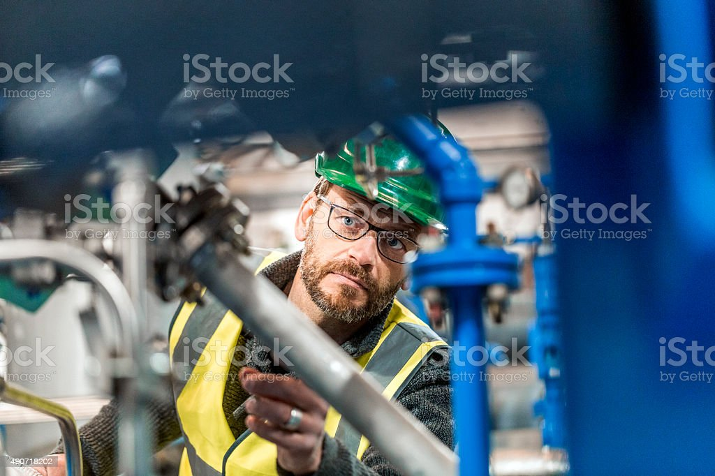 Manufacturing worker analysing machines at factory stock photo